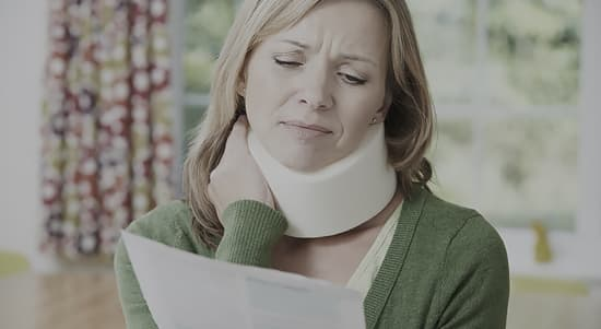 A lady with a neck brace in pain holding a letter